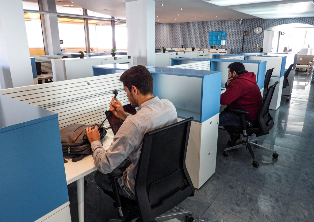 People sit in half-cubicles as they work at the Nuqta coworking space, which provides workstations, meeting rooms, and a cafeteria for small businesses and entrepreneurs in Libya's capital Tripoli on January 19, 2021.