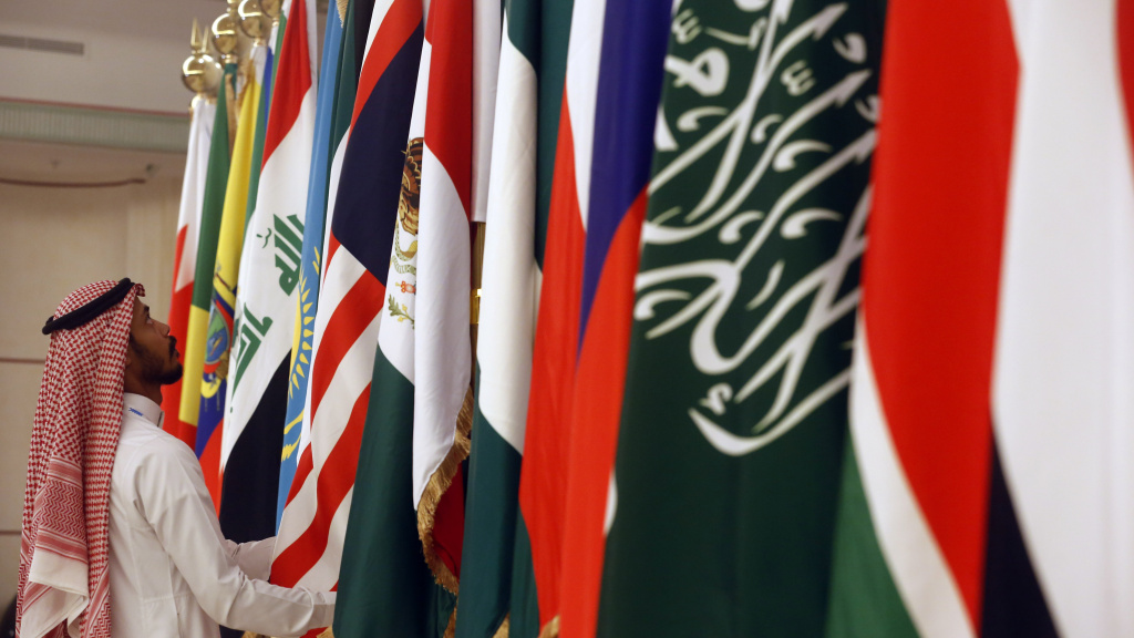 A Saudi worker adjusts flags of participating countries before a meeting of energy ministers from OPEC and its allies in Jeddah, Saudi Arabia, on May 19. OPEC+ countries met again in Vienna on Monday and Tuesday and agreed to formalize their relationship in a