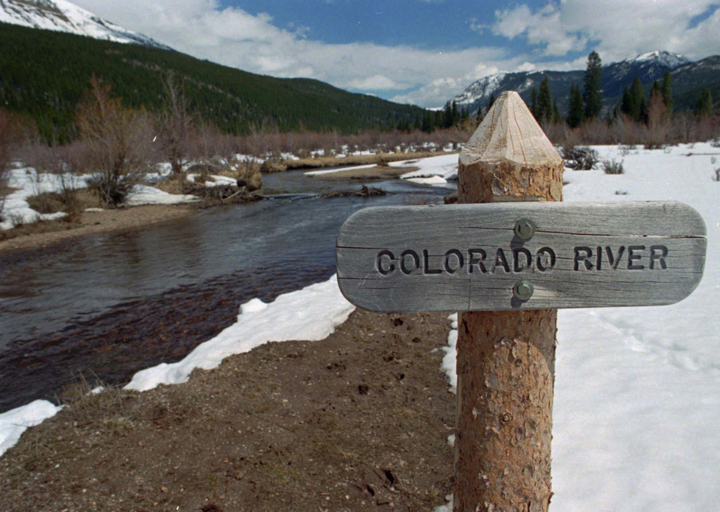 In this May 1, 1997 file photograph, sign marks the Colorado River as it flows past the Never Summer Mountains in Rocky Mountain National Park near the town of Grand Lake, Colo. The river serves about 40 million people and 6,300 square miles of farmland in Arizona, California, Colorado, Nevada, New Mexico, Utah and Wyoming. As of Tuesday, the accumulated snowfall was 104 percent of normal in the Upper Colorado River Basin.