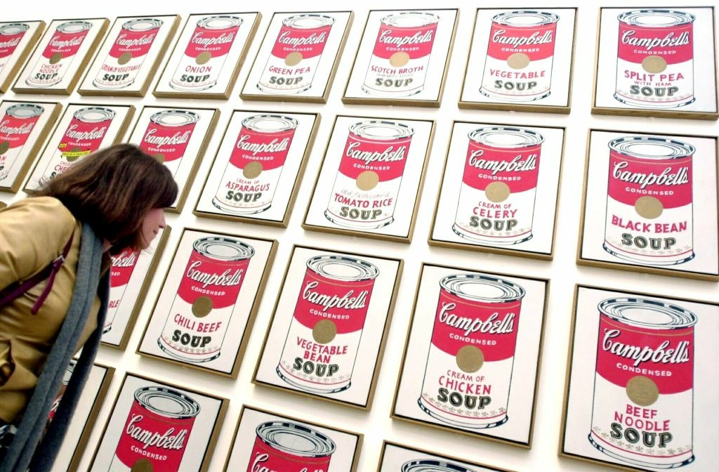 A visitor looks at enigmatic American artist Andy Warhol's 'Campbell's Soup Cans' at the Tate Modern in London 05 February 2002.