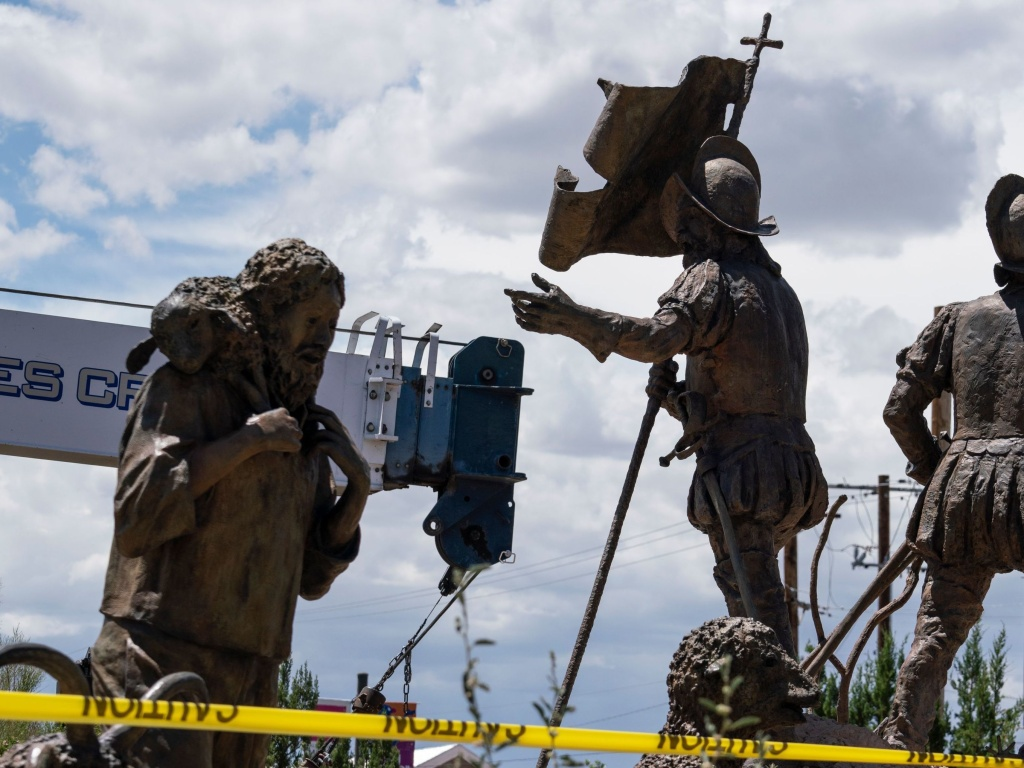 A sculpture of Juan de Onate's group of settlers colonizing New Mexico is pictured as workers for the City of Albuquerque remove a sculpture of Spanish conquistador Juan de Onate on Wednesday in Albuquerque, New Mexico. A man was shot a day before as a heavily armed militia group attempted to defend the statue from US protestors in New Mexico.