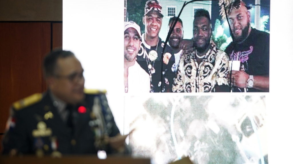 Director of the National Police General Ney Aldrin Bautista Almonte, projects a photograph taken of former Boston batter David Ortiz, second from right, on the night he was shot in Santo Domingo, Dominican Republic. Officials say a gunman shot Ortiz after mistaking him for Sixto David Fernández, not pictured.