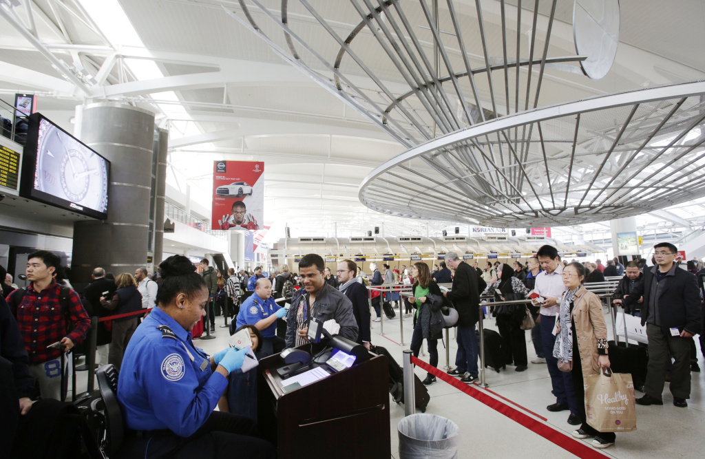In this Oct. 30, 2014, photo a TSA officer checks a passenger's ticket, boarding pass and passport as part of security screening at John F. Kennedy International Airport in New York.