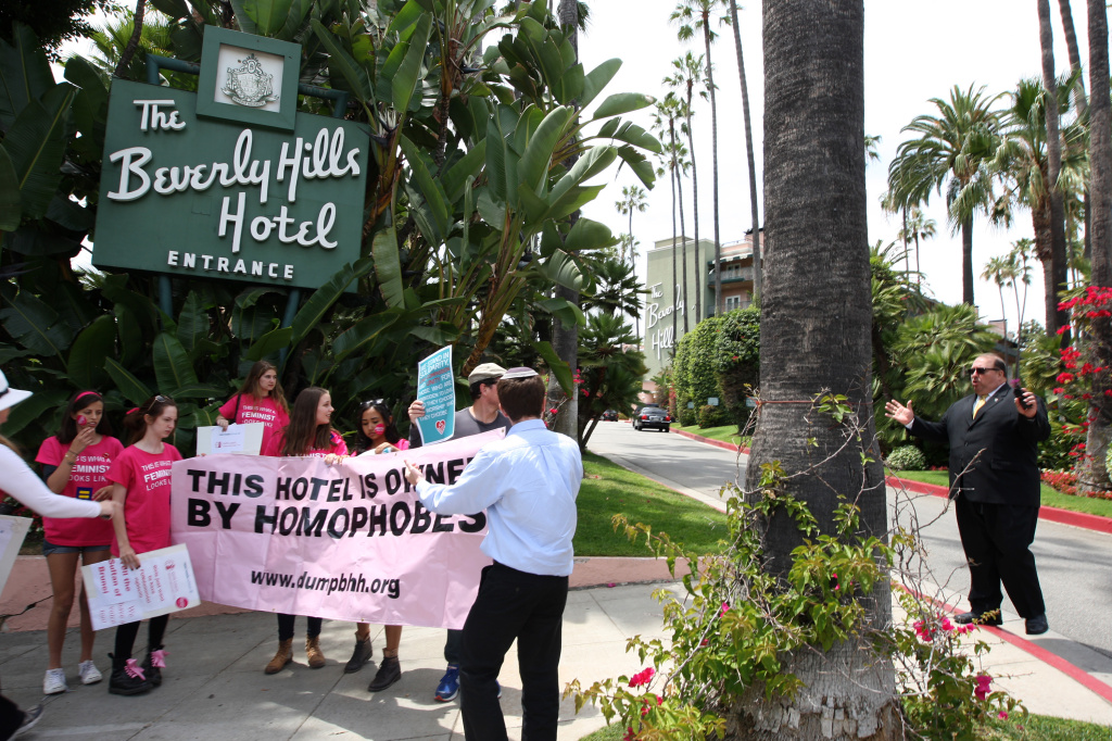 A security guard confronts demonstrators protesting draconian punishment of women and gay people announced by the Sultan of Brunei on a sideway near the entrance to the Beverly Hills Hotel, which is owned by the Sultan, on May 5, 2014 in Beverly Hills, California.