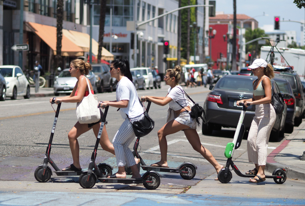 Young women ride shared electric scooters in Santa Monica, California, on July 13, 2018.