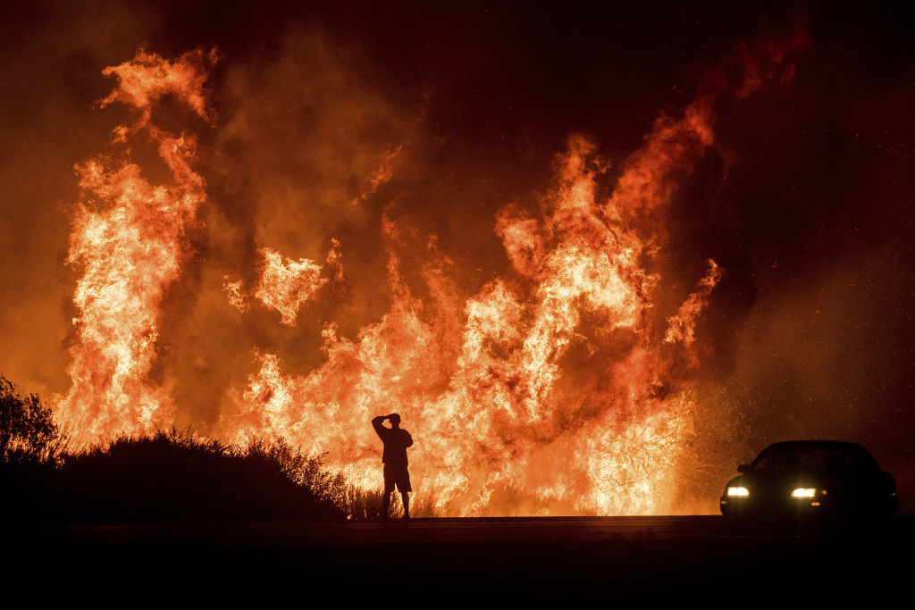 In this file photo, a motorist on Highway 101 watches flames from the Thomas fire leap above the roadway north of Ventura, Calif., on Wednesday, Dec. 6, 2017.