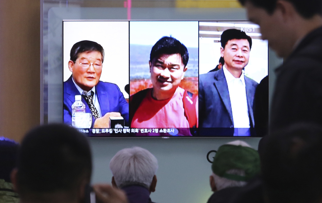 In this May 3, 2018 photo, people watch a TV news report on screen, showing portraits of three Americans, Kim Dong Chul, left, Tony Kim and Kim Hak Song, right, detained in the North Korea, at the Seoul Railway Station in Seoul, South Korea. President Donald Trump says Secretary of State Mike Pompeo is on his way back from North Korea with three American detainees, saying they