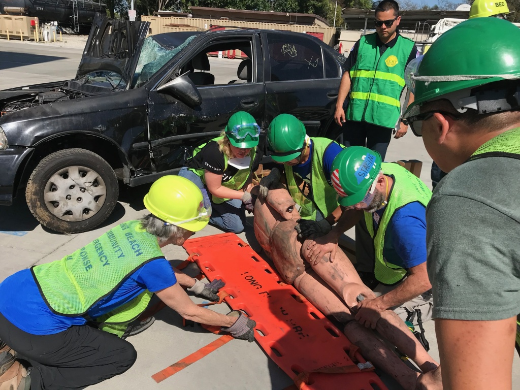 CERT trainees practice how to properly transport victims as they place a dummy victim on a stretcher.