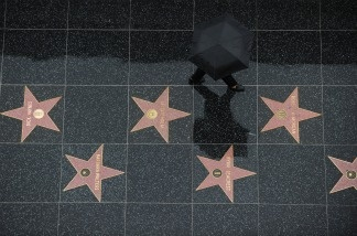 A tourist walks in the rain on the stars of the Hollywood Walk of Fame in Hollywood, California.