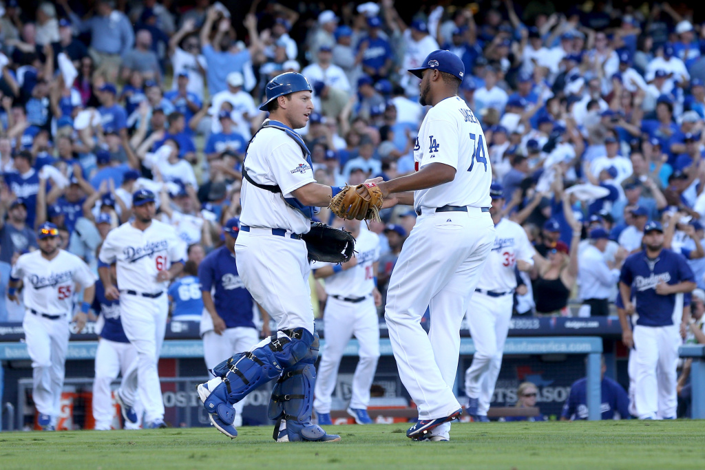 Kenley Jansen #74 and A.J. Ellis #17 of the Los Angeles Dodgers celebrate after the Dodgers defeat the St. Louis Cardinals 6-4 in Game Five of the National League Championship Series at Dodger Stadium on October 16, 2013 in Los Angeles, California.