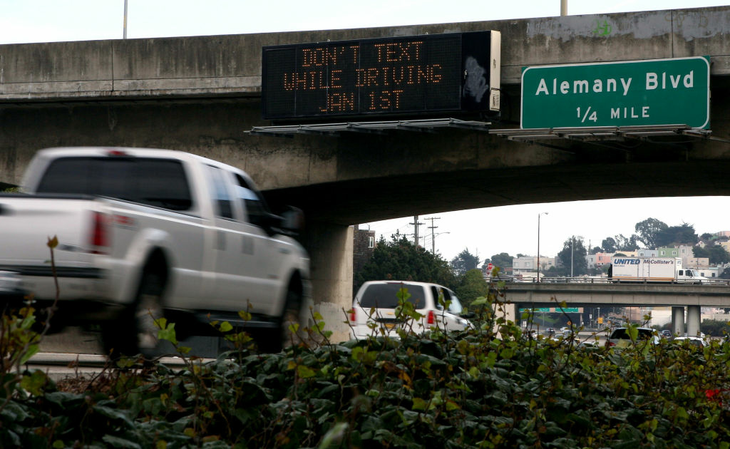 Cars drive by a sign notifying of a new texting while driving law on Interstate 280 in San Francisco, 2008. The law may not have stopped all drivers, but AT&T funded a new smart phone app that might.