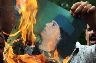 A Libyan protester burns a portrait of Libyan leader Moamer Kadhafi in front of the Libyan embassy in Kuala Lumpur on February 23, 2011. Some 200 protesters gathered in front of the embassy with banners and placards to condemn the bloody crackdown on anti-government demonstrators in Libya.