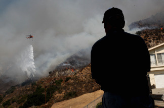 A local resident watches a firefighting helicopter drop water ahead of the Station Fire as it approaches homes August 31, 2009 in Tujunga, California.