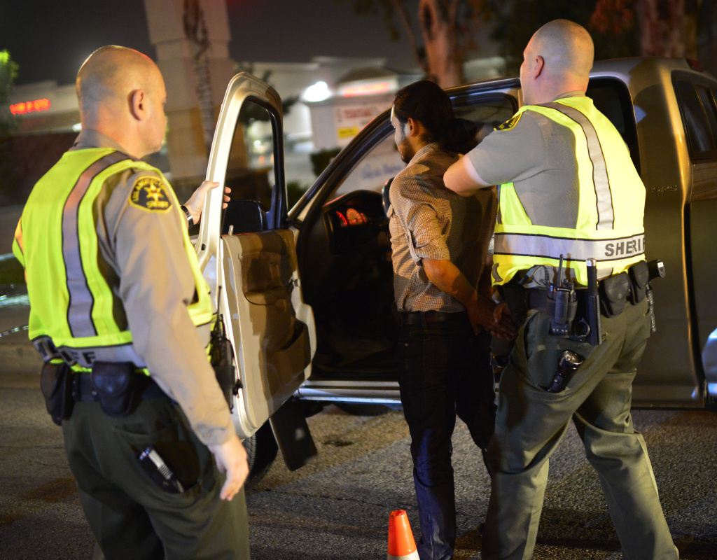 Los Angeles Sheriff's Department deputies stop a man at a DUI checkpoint in Bellflower. He was later released after passing a breathalyzer test.