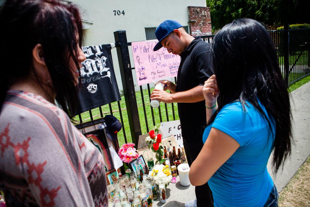 File: Alex, 18, lights a candle for his friend, Manuel Diaz. Diaz was shot and killed by Anaheim police on Saturday, July 21, 2012.