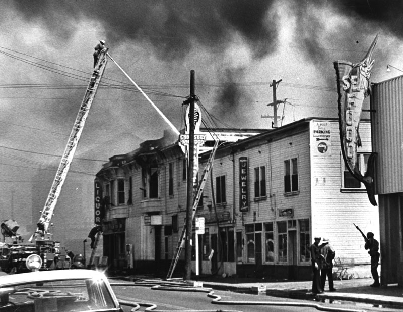 1965 Watts Riots: A fireman on a tall ladder aims water at fire on the rooftop of a building complex in Watts. Corner building has a liquor store, chop suey and seafood restaurant, and a jewelry store. Officers with rifles stand guard by the alley.