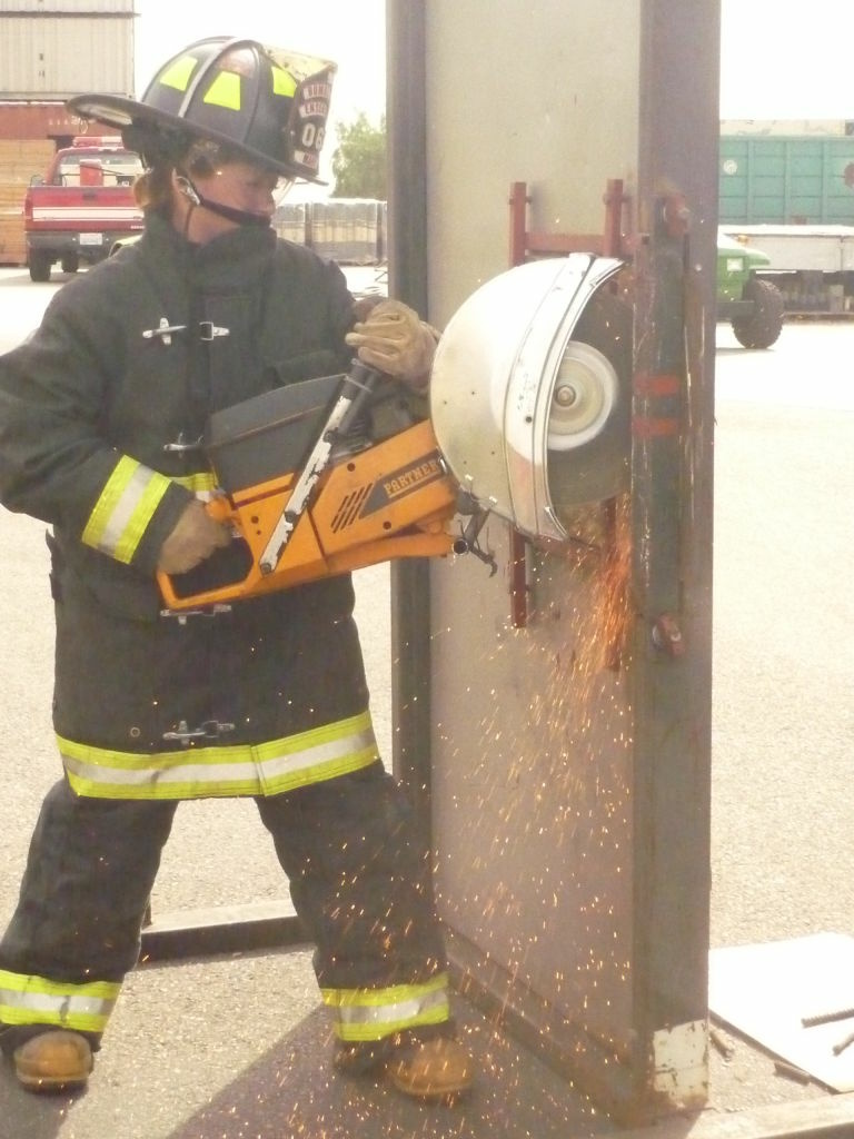 A Mexican firefighter practices using a rotary saw at an angle to cut open an iron door.  Los Angeles City firefighters covered the technique, along with other related material, in a free two-day workshop at their headquarters near Dodger Stadium.
