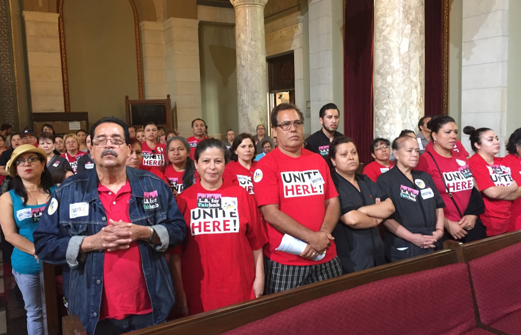 Hospitality workers with Unite Here Local 11 stand up as members call for tighter regulations on Airbnb and other short-term rental companies at a Los Angeles City Council planning committee meeting on June 13, 2017.