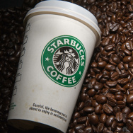 A Starbucks coffee cup and beans are see