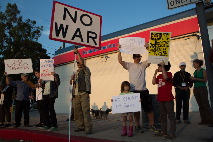 Sam Patrick of Glendale protests the possibility of war in Syria alongside the Landau family, Peter and his daughter Ada.