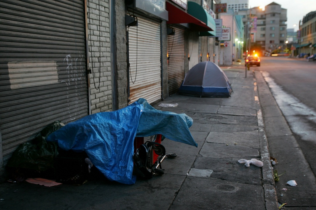 A police car stops near homeless people sleeping in their encampments in the early morning hours of downtown sidewalks on April 19, 2006 in Los Angeles, California.