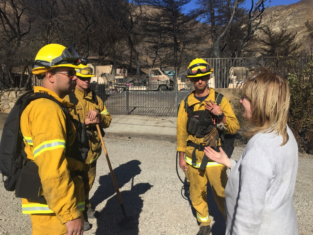 Carol Van Dusen (right) thanks San Francisco firefighters working to douse hot spots near her home in the Kagel Canyon neighborhood near Sylmar. The Creek Fire destroyed several homes up the road from Van Dusen's house.