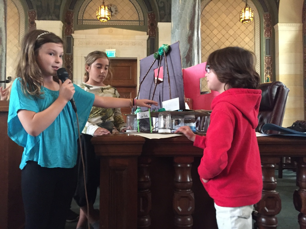 Emma Allison, a fourth grader at Los Feliz Charter School for the Arts, presents her group's model that would reuse kitchen waste water for plants.