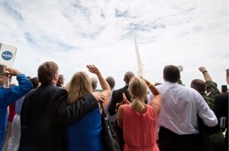 Guests look on from the terrace of Operations Support Building II as space shuttle Atlantis launches from launch pad 39A on the STS-135 mission on July 8, 2011 at the NASA Kennedy Space Center in Cape Canaveral, Florida.