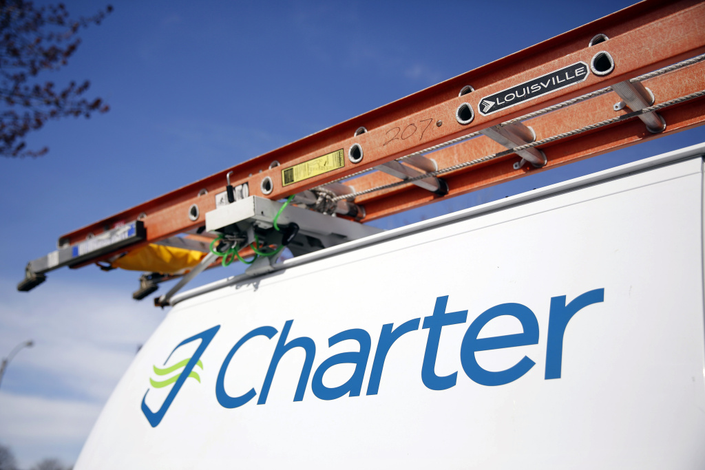 This April 1, 2015 photo shows a Charter Communications van in St. Louis. Charter Communications is close to buying Time Warner Cable for about $55 billion, two people familiar with the negotiations said Monday, May 25, 2015. (AP Photo/Jeff Roberson)
