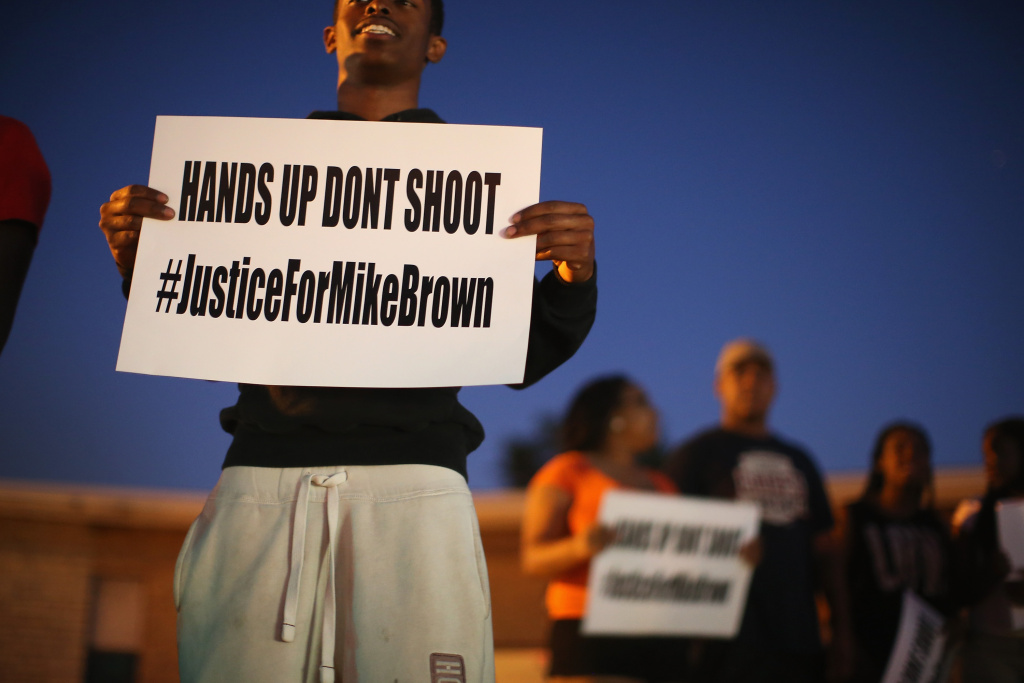 ST. LOUIS, MO - AUGUST 12:  Demonstrators protest the killing of teenager Michael Brown outside Greater St. Marks Family Church while Brown's family along with civil rights leader Rev. Al Sharpton and a capacity crowd of guests met inside to discuss the killing on August 12, 2014 in St Louis, Missouri. Brown was shot and killed by a police officer on Saturday in the nearby suburb of Ferguson. Ferguson has experienced two days of violent protests since the killing but, tonight the town remained mostly peaceful.  (Photo by Scott Olson/Getty Images)