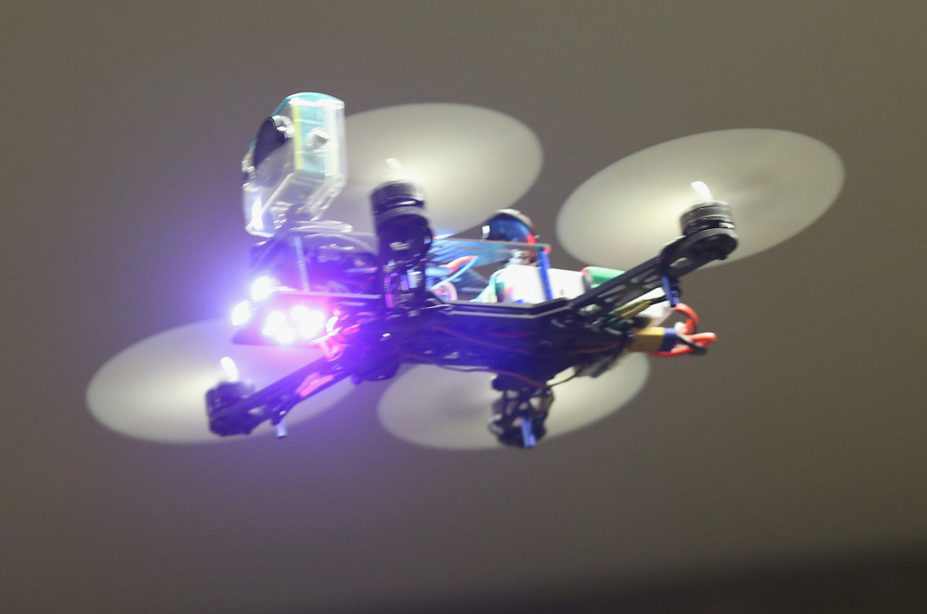 A mini quadcopter drone meant for FPV racing flies in a hall during a gathering of drone enthusiasts.