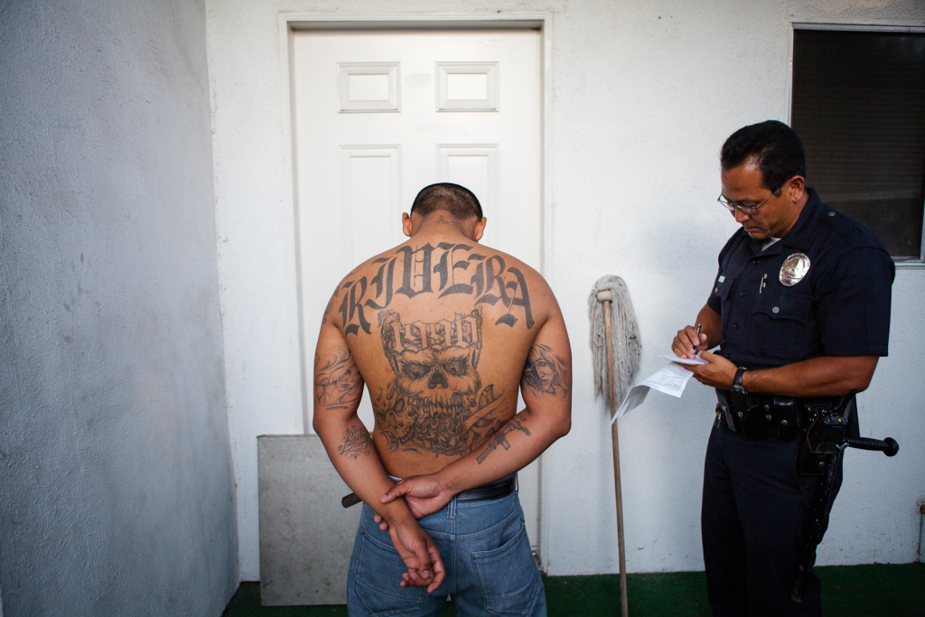 Officer Craig Suzuki takes information from a young gang member. In an example of some of the miscommunications that can happen with between departments with the new prison realignment system, the Unit meant only to verify the man's address (a prerequisite for release) and was surprised to find him home — after having been freed a year ago.