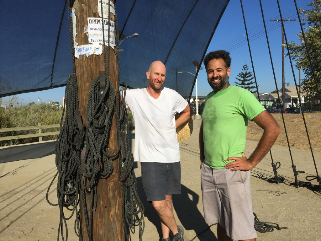 Joshua Callaghan, left, and Daveed Kapoor, right, with their sculpture, Mast, which is part of LA's public art biennial, CURRENT:LA. The sculpture is made of an actual telephone pole, complete with neighborhood flyers.