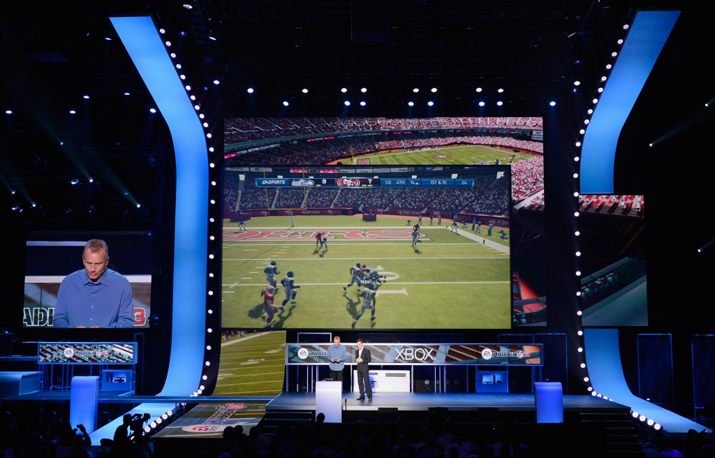 NFL Hall of Fame quarterback Joe Montana (L) plays the EA Sports Madden 13 game as EA Sports as Executive Vice President, EA Sports Andrew Wilson looks on.