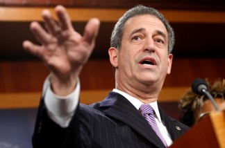 U.S. Sen. Russell Feingold (D-WI), shown here during a news conference on Capitol Hill in 2009, is locked in a close race for re-election against Republican Ron Johnson. Both have campaign ads spinning their stance on the new health care law.