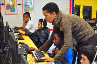 FILE - A Compton Unified School District curriculum specialist assists a student in Tibby Elementary's computer lab.