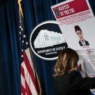 A staff member reveals a wanted poser of Igor Anatolyevich Sushchin, one of three Russians charged for in the 2014 hacking of Yahoo, during a press conference at the US Department of Justice on March 15, 2017 in Washington, DC.