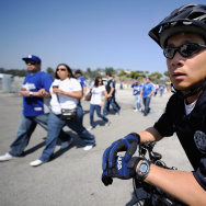 File: A Los Angeles Police Department officer on a bicycle patrols the parking lot of Dodger Stadium prior to the home opener against the Pittsburgh Pirates.