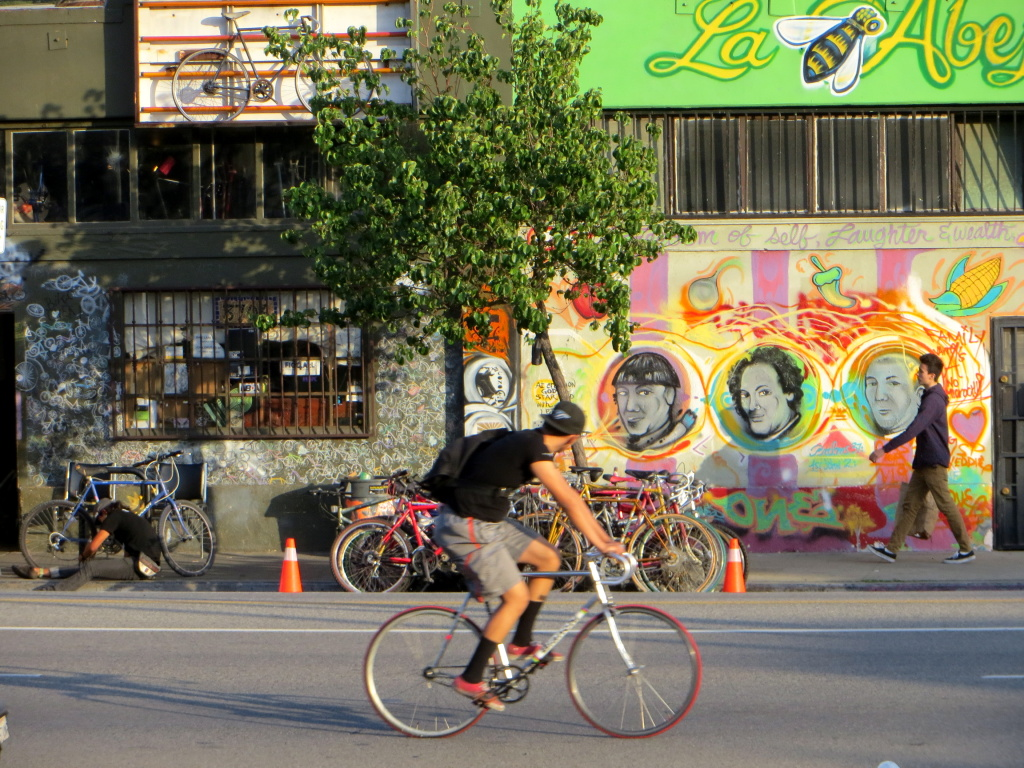 A cyclist passes community bicycle repair shop, The Bike Oven in Highland Park, Los Angeles.