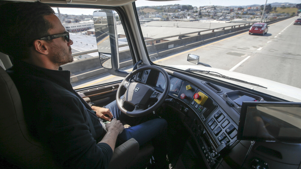 Two years after Uber paid $680 million to buy the self-driving truck startup Otto, the company is folding that effort. In this photo from 2016, an Otto engineer sits behind the steering wheel of a self-driving, big-rig truck during a demonstration in San Francisco.