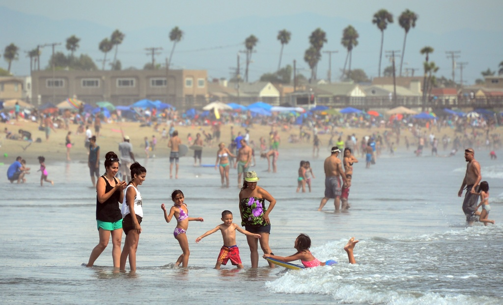 File: A girl catches a wave on her boogie board for her family to see as crowds took to southern California beaches on the Labor Day holiday on Sept. 2, 2013 in California. Though Labor Day took its name from its origins in the labour union movement and is an annual holiday to celebrate workers achievements, the day which falls every year on the first Monday of September is mostly considered a day to mark the end of summer across the U.S.