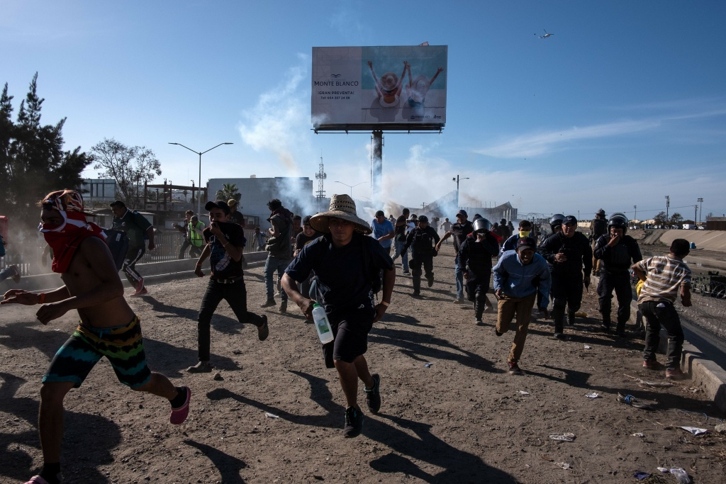Central American migrants -mostly Hondurans- run along the Tijuana River near the El Chaparral border crossing in Tijuana, Baja California State, Mexico, near US-Mexico border, after the US border patrol threw tear gas from the distance to disperse them after an alleged verbal dispute, on November 25, 2018.