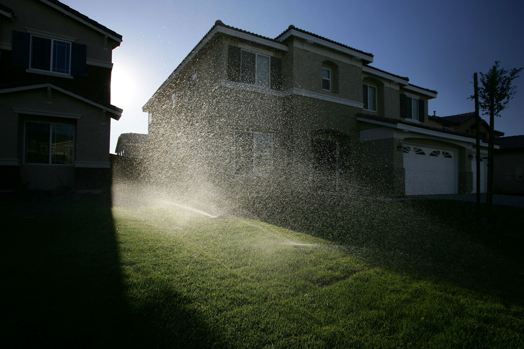 Sprinklers water the lawns of a new housing development July 28, 2005 in Hesperia, California. Half of all the water used by inland homeowners goes to irrigating yards compared to one third or less in the cooler coastal regions.