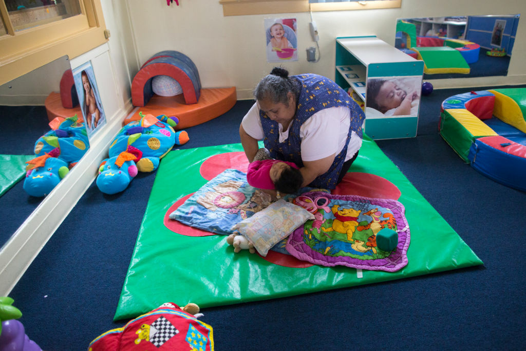 Rosa Sanchez lays down a child to rest at Jardín de Niños, which is part of the California Children's Academy, a large child care agency. It helps families become financially independent by providing affordable child care to low-income families.