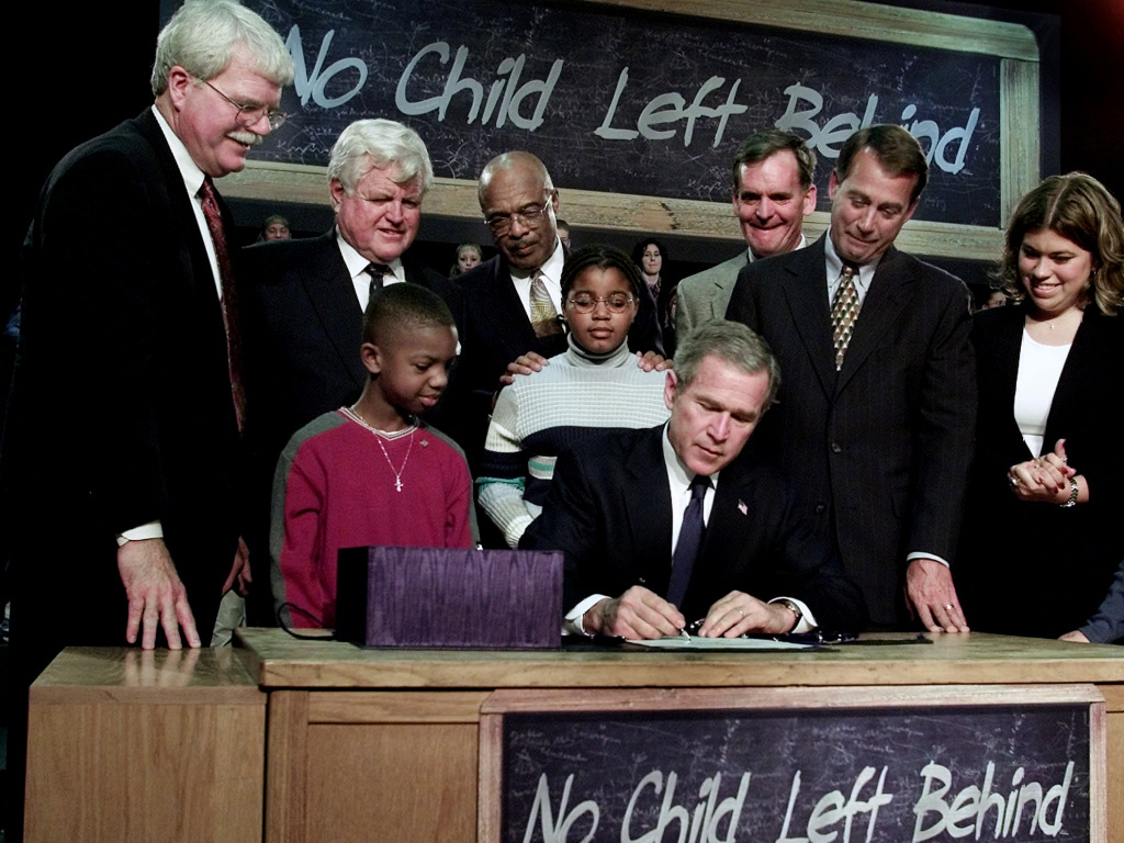 File: President George W. Bush, seated, signs No Child Left Behind into law at Hamilton High School in Hamilton, Ohio.