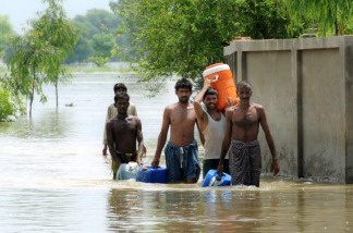 Pakistani flood survivors return to higher ground after getting drinking water in the flooded area of Pathan Wala on August 16, 2010