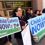 Los Angeles County social workers display a banner calling for children's safety in Los Angeles on October 28, 2013.