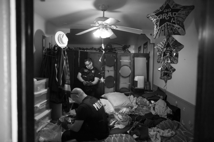 Detective Jones looks for clues in the bedroom of a home in Corona, Calif. The mirror in the bedroom has Los Angeles gang tags.
