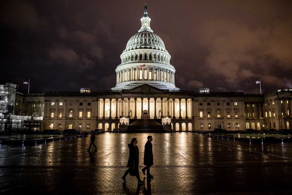 People walk along the east front plaza of the US Capitol at night.