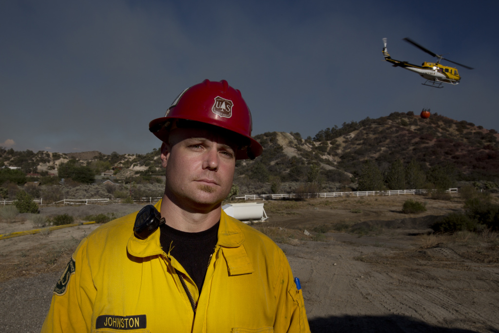 Captain Ryan Johnston of the United States Forest Service stands by as a helicopter replenishes its water supply at the Hillside Community Church in Wrightwood, California on August 18th, 2016.
